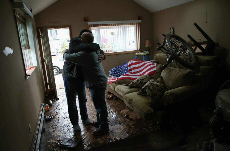 Homeowner Michael Russo (R) is comforted by friend Joseph Bono on November 1, 2012 in the Ocean Breeze area of the Staten Island borough of New York City. The first floor of Russo's home was completely flooded by the ocean surge caused by superstorm Sandy. Russo said that he salvaged an American flag he had stored on the upper shelf of a supply closet. Photo: John Moore, Getty Images / 2012 Getty Images