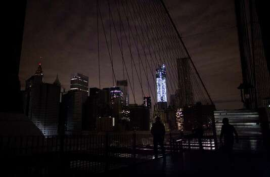 Much of lower Manhattan remains dark, as viewed from the darkened Manhattan side of the pedestrian walkway of the Brooklyn Bridge, Thursday, Nov. 1, 2012 in New York. In the wake of superstorm Sandy, power outages still plague much of the New York area. Photo: Craig Ruttle, Associated Press / FR61802 AP