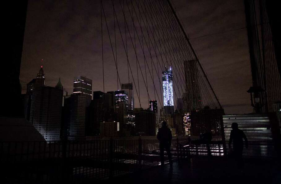 Much of lower Manhattan remains dark, as viewed from the darkened Manhattan side of the pedestrian w