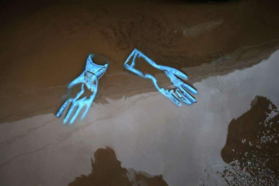 The gloves from rescue workers lie in floodwaters outside a house where the bodies of two elderly people were reportedly found on November 2, 2012 in the Staten Island borough of New York City. Rescue personel and police continue to find drowning victims from Hurricane Sandy four days after the storm. Meanwhile, hundreds of thousands of people in Staten Island remained without electricity in areas affected by the superstorm. Photo: John Moore, Getty Images / 2012 Getty Images