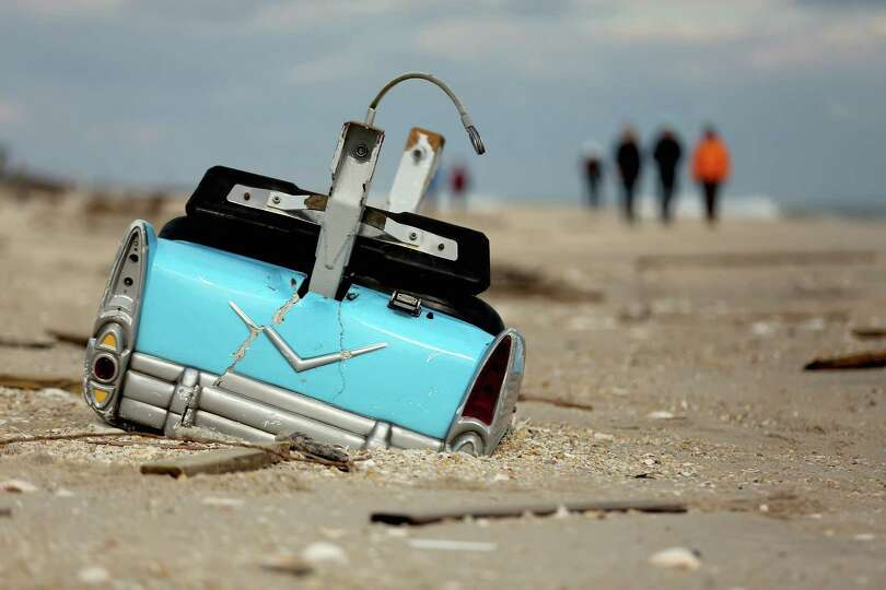 A dislodged amusement park bumper car is partially submerged in the sand following Superstorm Sandy