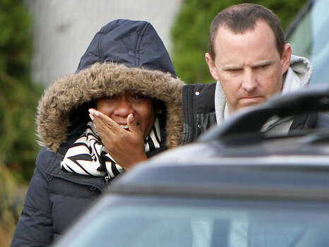 Glenda Moore, and her husband, Damian Moore, react as they approach the scene where at least one of their childrens' bodies were discovered in Staten Island, New York, Thursday, Nov. 1, 2012. Brandon Moore, 2, and Connor Moore, 4, were swiped into swirling waters as their mother tried to escape her SUV on Monday amid rushing waters that caused the vehicle to stall during Superstorm Sandy.  Police said the mother, Glenda Moore, was going to her sister's home in Brooklyn when she tried to flee the vehicle with the boys, only to have the force of the rising water and the relentless cadence of pounding waves rip the boy's small arms from her. Photo: Seth Wenig, Associated Press / AP