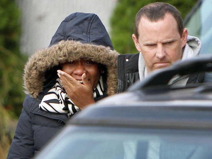 Glenda Moore, and her husband, Damian Moore, react as they approach the scene where at least one of