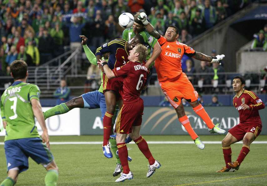 Real Salt Lake goalie Nick Rimando swats a ball kicked by Mauro Rosales away from the goal during