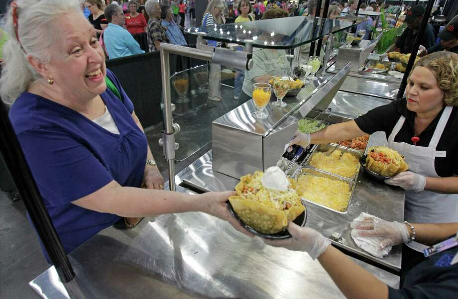 Suzanne Lindsay, left,  of Ft. Lauderdale picks up her taco salad as worker Judy Delgado, right, prepares another salad in the food court during the International Quilt Festival at the George R Brown Convention Center, 1001 Avenida de las Americas, Thursday, Nov. 1, 2012, in Houston.  The food court is filled with options including new items of a cupcake truck and a grilled cheese station. Each year, the food court serves more than 8,000 baked potatoes and 7,000 taco salads. Photo: Melissa Phillip, Houston Chronicle / © 2012 Houston Chronicle