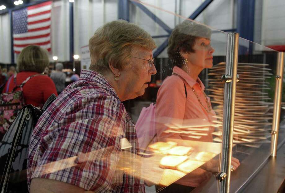 Nancy Prisner, left, of Magnolia and Mary Pesek, right, of Spring make a select at the Souper Cheese, a grilled cheese station, in the food court during the International Quilt Festival at the George R Brown Convention Center, 1001 Avenida de las Americas, Thursday, Nov. 1, 2012, in Houston.  The food court is filled with options including new items of a cupcake truck and a grilled cheese station. Each year, the food court serves more than 8,000 baked potatoes and 7,000 taco salads. Photo: Melissa Phillip, Houston Chronicle / © 2012 Houston Chronicle