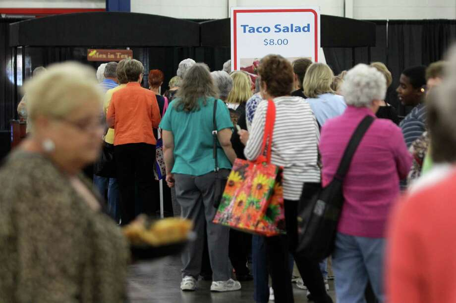 Customers wait in a long line for taco salad in the food court during the International Quilt Festival at the George R Brown Convention Center, 1001 Avenida de las Americas, Thursday, Nov. 1, 2012, in Houston.  The food court is filled with options including new items of a cupcake truck and a grilled cheese station. Each year, the food court serves more than 8,000 baked potatoes and 7,000 taco salads. Photo: Melissa Phillip, Houston Chronicle / © 2012 Houston Chronicle