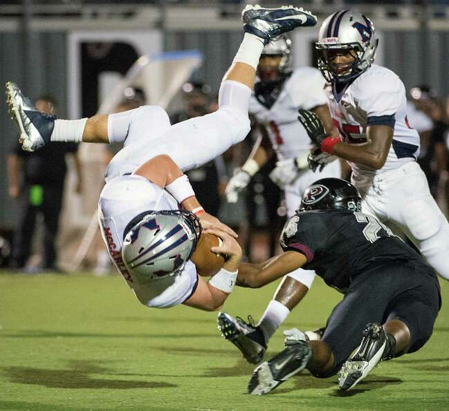 Manvel quarterback Shane McCarley (3) is upended by Pearland defensive back Cornelius Barber (26) du