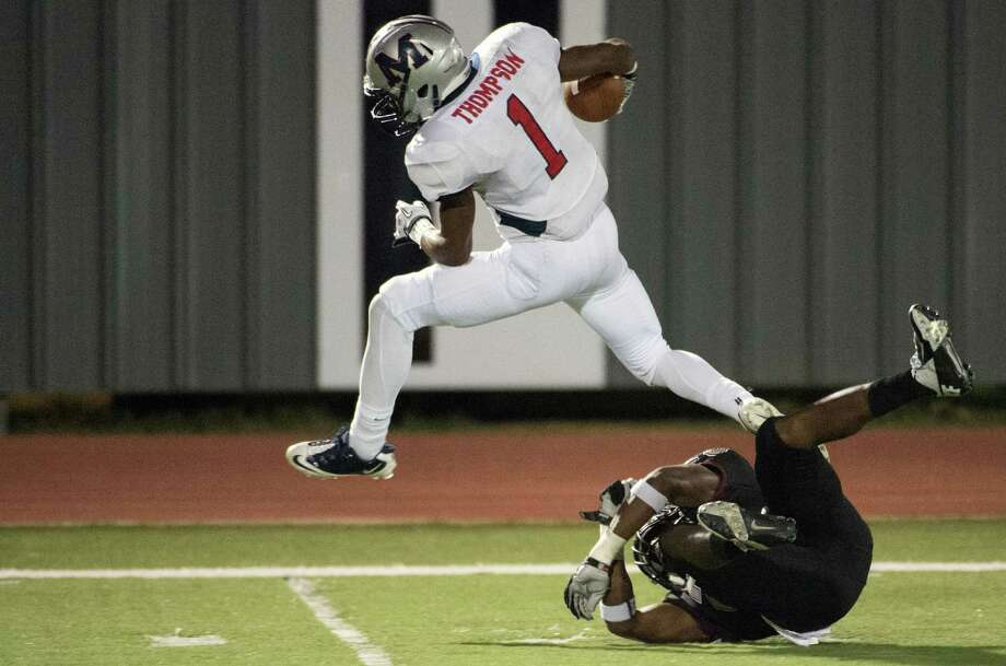 Manvel wide receiver Carlos Thompson (1) leaps over Pearland defensive back Marlon Walls (28) on a 64-yard touchdown during the first quarter of a high school football game at The Rig on Friday, Nov. 2, 2012, in Pearland. Photo: Smiley N. Pool, Houston Chronicle / © 2012  Houston Chronicle