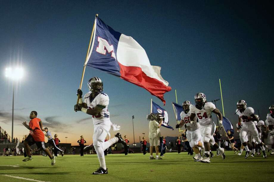 Manvel defensive back Gary Haynes (20) carries the flag as he leads the Mavericks as they take the field to face Pearland in a high school football game at The Rig on Friday, Nov. 2, 2012, in Pearland. Photo: Smiley N. Pool, Houston Chronicle / © 2012  Houston Chronicle