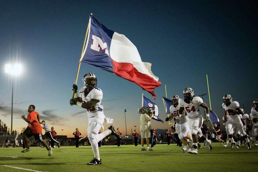Manvel defensive back Gary Haynes (20) carries the flag as he leads the Mavericks as they take the f