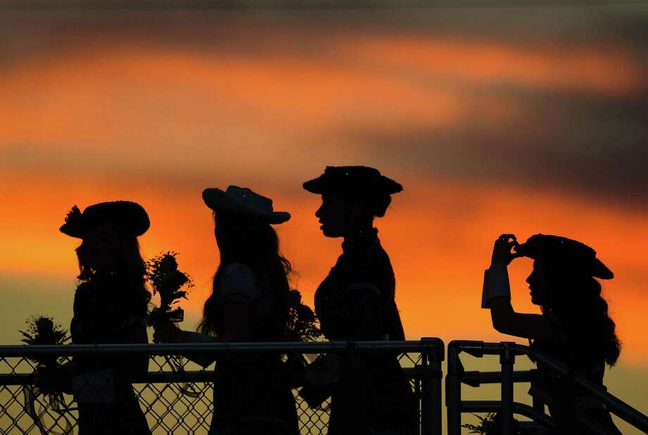 Members of the Pearland Prancers drill team head for the stands as the sun sets before a high school football game against Manvel at The Rig on Friday, Nov. 2, 2012, in Pearland. Photo: Smiley N. Pool, Houston Chronicle / © 2012  Houston Chronicle