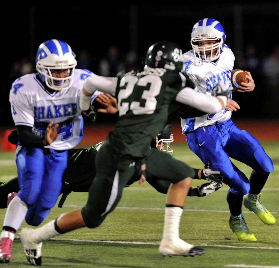 Shaker's Tyler Oppelt (14), right, runs the ball with help from Kenny Jackson (34), left, as Shen's Kyle Buss (23) defends during their Class AA Super Bowl football game on Friday, Nov. 2, 2012, at Shenendehowa High in Clifton Park, N.Y. (Cindy Schultz / Times Union) Photo: Cindy Schultz / 00019908A