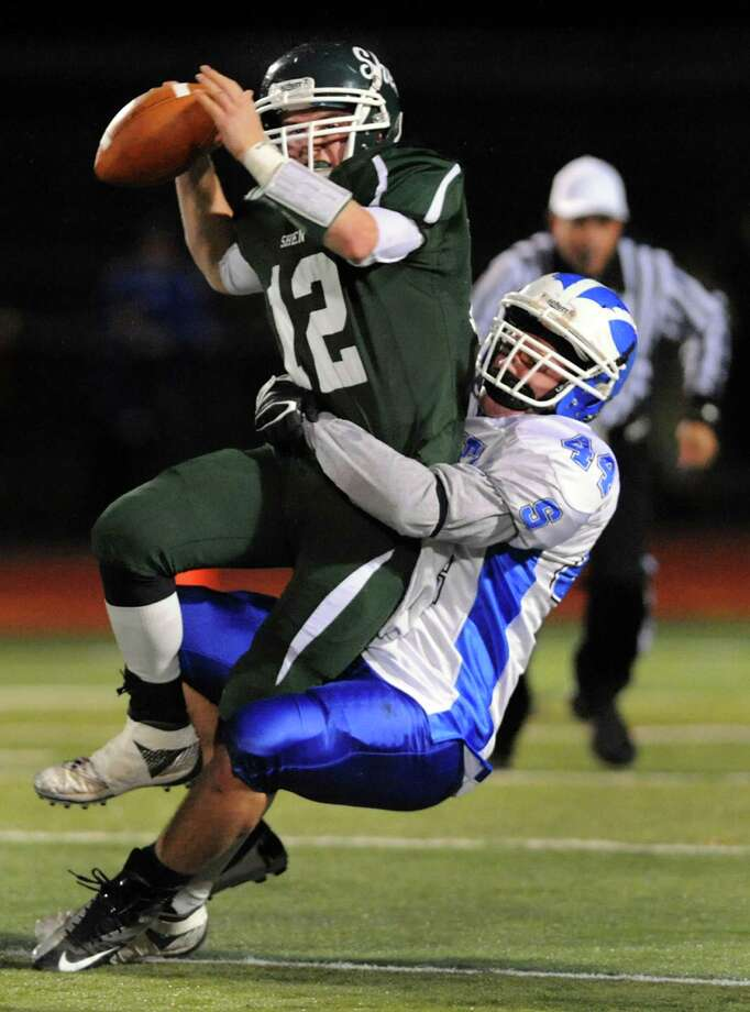 Shaker's Dylan Quay (44), right, sacks Shen's quarterback Ryan Buss (12) during their Class AA Super Bowl football game on Friday, Nov. 2, 2012, at Shenendehowa High in Clifton Park, N.Y. Buss tried to get a pass off and received an intentional grounding penalty. (Cindy Schultz / Times Union) Photo: Cindy Schultz / 00019908A