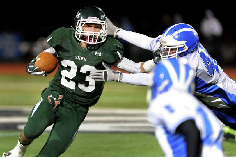 Shen's Kyle Buss (23), right, stiff arms Shaker's Brandon Safford (42) during their Class AA Super B