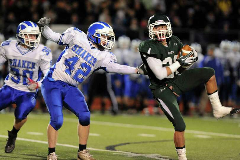 Shen's Kyle Buss (23), right, hauls in a pass as Shaker's Brandon Safford (42), center, defends duri
