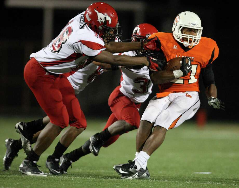La Porte running back Keith Whitely (21) is tackled by North Shore's (l to r) Isaiah Freeman, Tim Broden and Chris Russell during the second half of a high school football game, Friday, November 2, 2012 at Bulldog Stadium in La Porte, TX. Photo: Eric Christian Smith, For The Chronicle