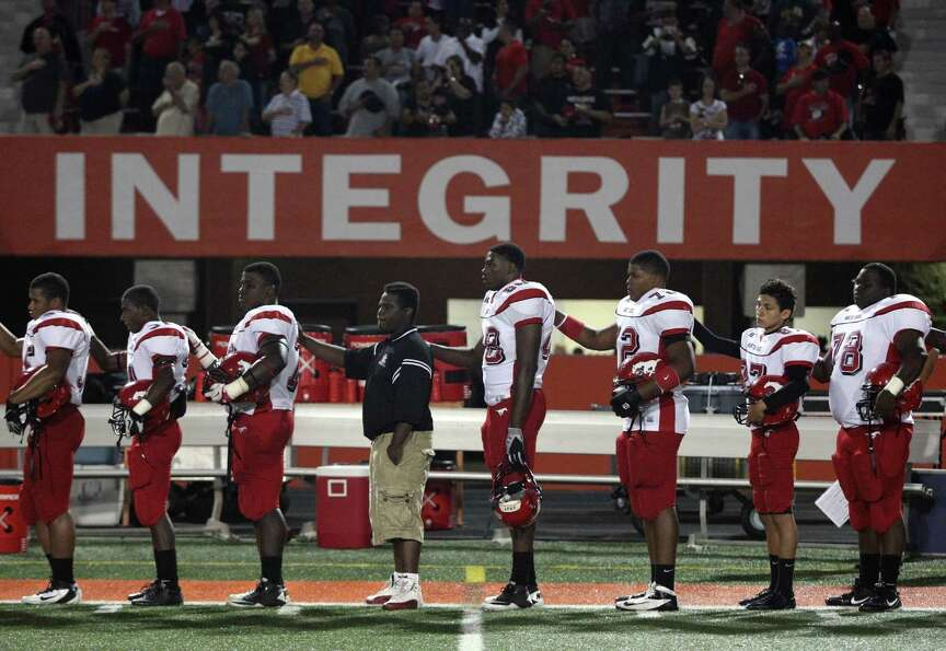 The North Shore Mustangs stand during the National Anthem before a high school football game against