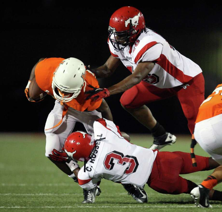 La Porte running back Johnathan Lewis is tackled for a loss by North Shore defensive back Chris Russell (3) and defensive end Isaiah Freeman during the first half of a high school football game, Friday, November 2, 2012 at Bulldog Stadium in La Porte, TX. Photo: Eric Christian Smith, For The Chronicle