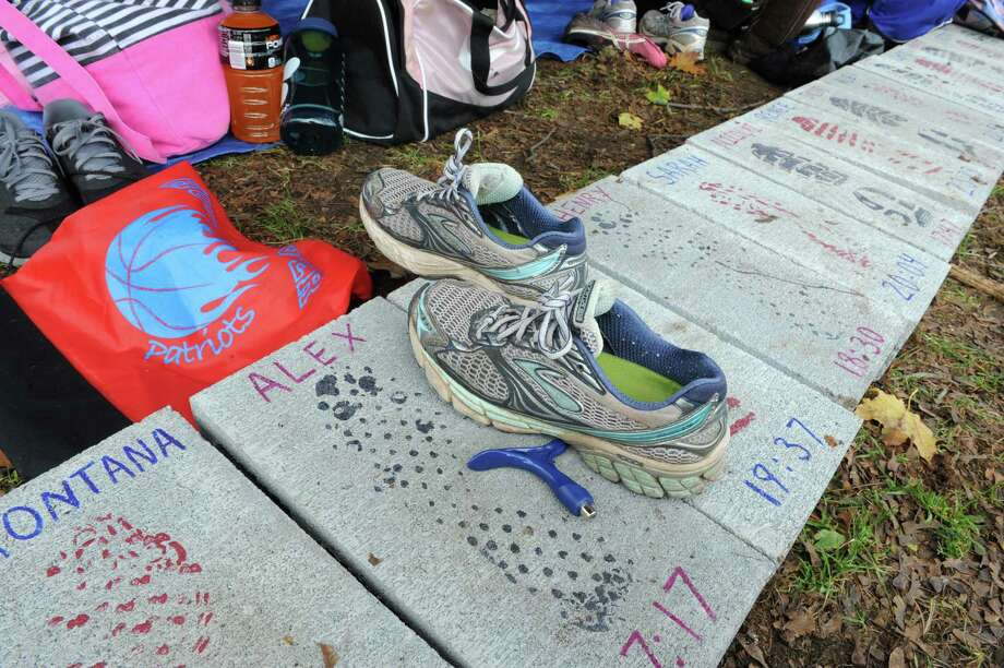 Sneakers rest on slabs with runners names and goal times at the Broadalbin-Perth High School compound tent at the Section II Cross Country Championships on Friday Nov. 2, 2012 in Saratoga Springs, N.Y.  (Lori Van Buren / Times Union) Photo: Lori Van Buren