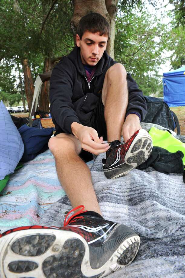 Aaron Alvarez laces up his sneakers before warming up with his teammates during the Section II Cross Country Championships on Friday Nov. 2, 2012 in Saratoga Springs, N.Y.  (Lori Van Buren / Times Union) Photo: Lori Van Buren