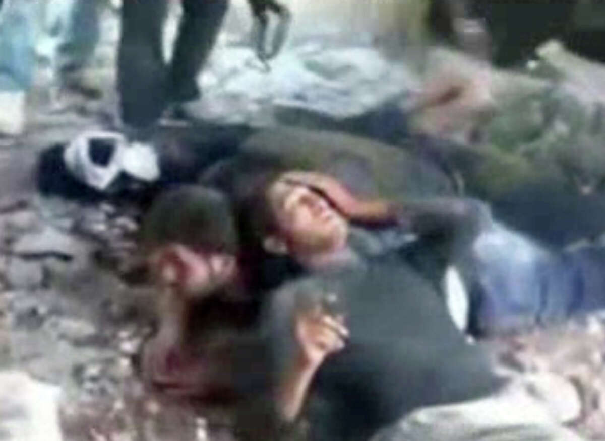 In this frame grab from amateur video taken Thursday, Nov. 1, 2012, and provided by the Syrian Observatory for Human Rights via AP video, captured soldiers lie on the ground in Saraqeb, northern Syria. Later in the video, alleged rebels appear to kill the group of captured soldiers, spraying them with bullets as they lie on the ground. This image from video obtained from the Syrian Observatory for Human Rights has been authenticated based on the video and audio translated and content checked by regional experts against known locations and events, as well as being consistent with independent AP reporting. (AP Photo/Syrian Observatory for Human Rights via AP video)