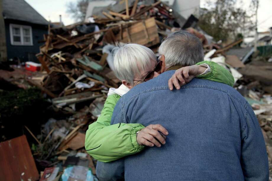 Sheila and Dominic Traina hug in front of their home which was demolished during Superstorm Sandy in Staten Island, N.Y., Friday, Nov. 2, 2012.  Mayor Michael Bloomberg has come under fire for pressing ahead with the New York City Marathon. Some New Yorkers say holding the 26.2-mile race would be insensitive and divert police and other important resources when many are still suffering from Superstorm Sandy. The course runs from the Verrazano-Narrows Bridge on hard-hit Staten Island to Central Park, sending runners through all five boroughs. The course will not be changed, since there was little damage along the route.  (AP Photo/Seth Wenig) Photo: Seth Wenig