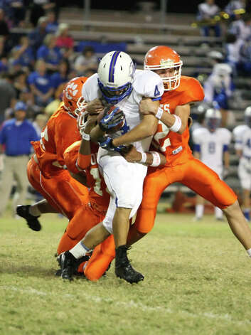 Buna running back Matthew Biddle, No. 4, is tackled by several Orangefield players during the game Friday at F.L. McClain Stadium in Orangefield. (Matt Billiot/Special to the Enterprise)