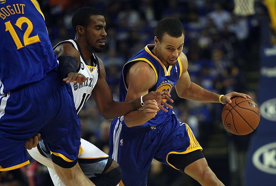 Warriors Stephen Curry drives by Grizzlies Mike Conley during the first half as the Golden State War
