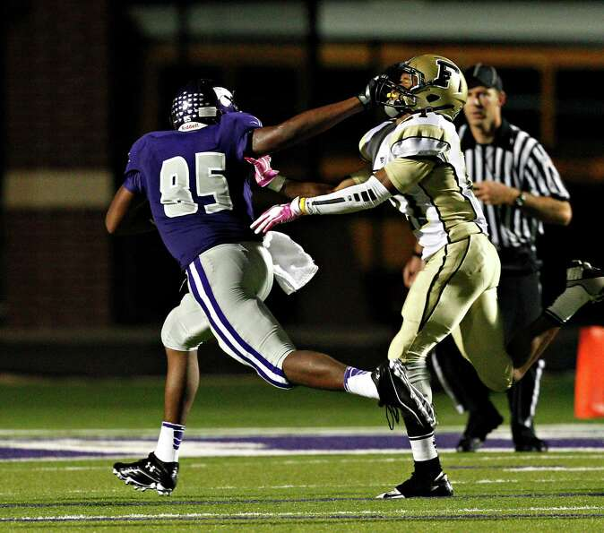 Angleton wide receiver Michael Thomas #85 gives Foster's Eric Jones #21 a stiff arm as he scores on