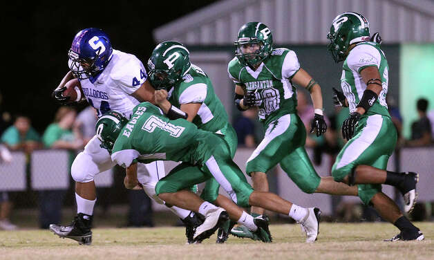 Somerset's Salvador Marines (44) hauls along the pair of Pleasanton defenders Jason Mills (07) and Nathan Contreras (03) as he runs upfield in high school football in Pleasanton on Friday, Nov. 2, 2012. Photo: Kin Man Hui, Express-News / © 2012 San Antonio Express-News
