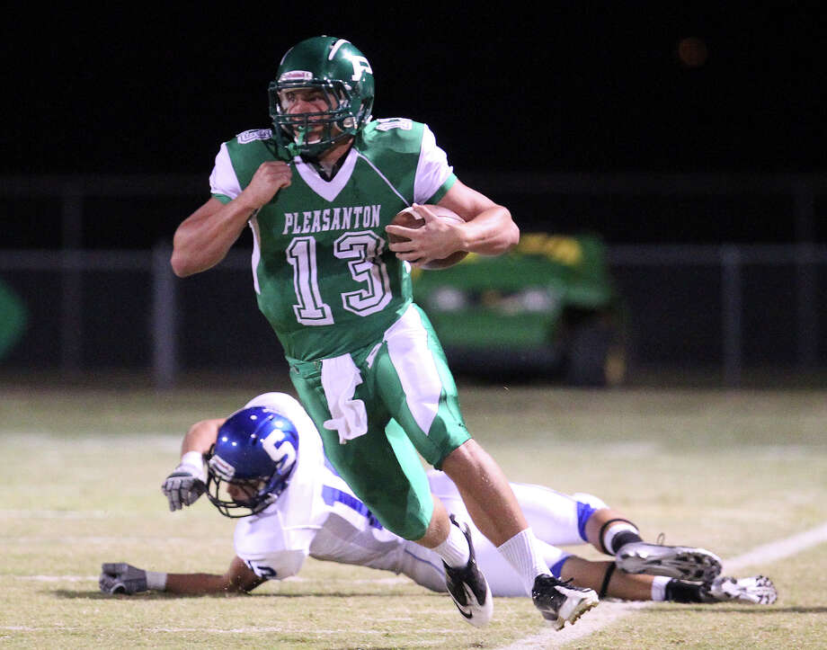 Pleasanton quarterback Luke Walters (13) runs with the ball against Somerset's Zachary Wiseman (12) in high school football in Pleasanton on Friday, Nov. 2, 2012. Photo: Kin Man Hui, Express-News / © 2012 San Antonio Express-News