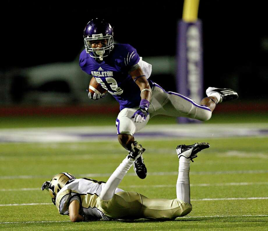 Angleton's Joshawa West  #23 hurdles over Foster's Truett Long #8 during a 24-4A high school football playoffs between Foster and Angleton, Friday, November 2, 2012 in Angleton, Texas. Photo: Bob Levey, Houston Chronicle / ©2012 Bob Levey