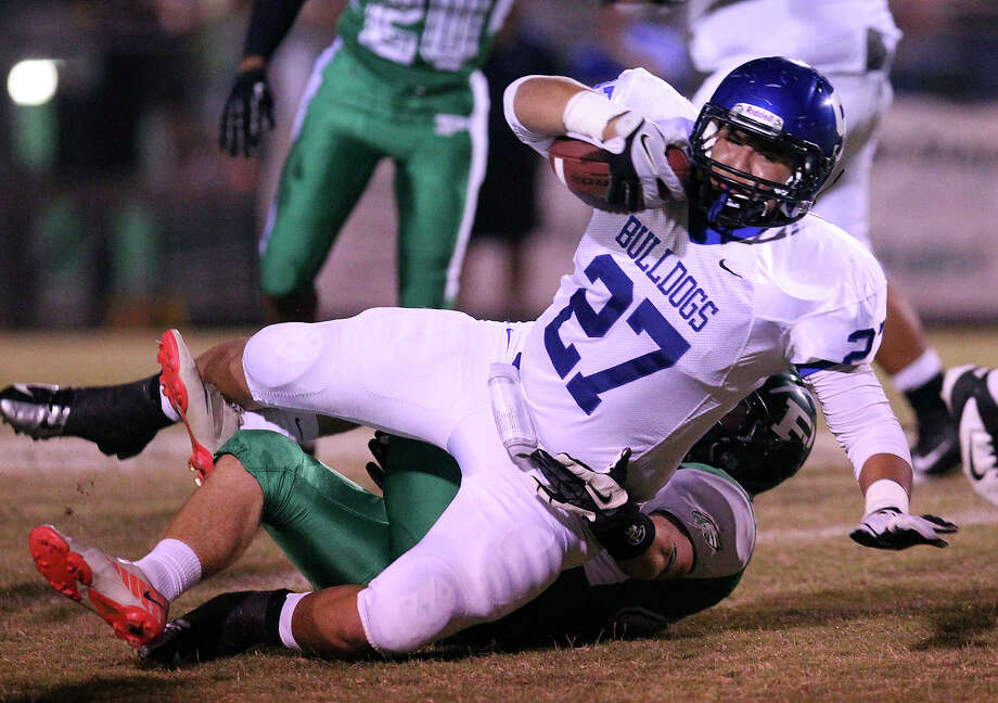 Somerset's Donaldo Perez (27) rolls over a Pleasanton defender in high school football in Pleasanton on Friday, Nov. 2, 2012. Photo: Kin Man Hui, Express-News / © 2012 San Antonio Express-News
