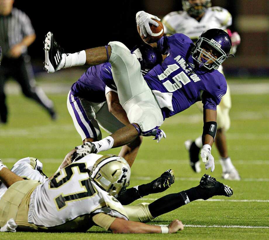Angleton running back Richard Cooper #15 is tripped up by Foster's Khane Mitchell #57 during a 24-4A high school football playoffs between Foster and Angleton, Friday, November 2, 2012 in Angleton, Texas. Photo: Bob Levey, Houston Chronicle / ©2012 Bob Levey