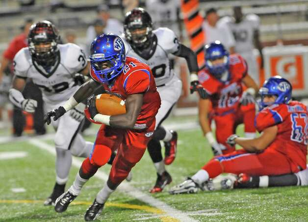 "West Brook Bruin #21, Cameron McBride, left, heads for a hole that his teammates opened up for him to run through. The West Brook Bruins hosted the Port Arthur Memorial Titans football team Friday night at the Carrol A.""Butch"" Thomas Educational Support Center Beaumont.  This was a District 21-5A game. At the half, the score was the Titans 35, the Bruins 10.  Dave Ryan/The Enterprise"