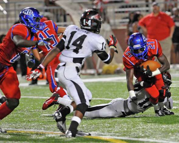 "West Brook Bruin #21, Cameron McBride, right, gets taken down for a loss by Titan defender #11, Melbrodrick Matthews.  The West Brook Bruins hosted the Port Arthur Memorial Titans football team Friday night at the Carrol A.""Butch"" Thomas Educational Support Center Beaumont.  This was a District 21-5A game. At the half, the score was the Titans 35, the Bruins 10.  Dave Ryan/The Enterprise Photo: Dave Ryan"