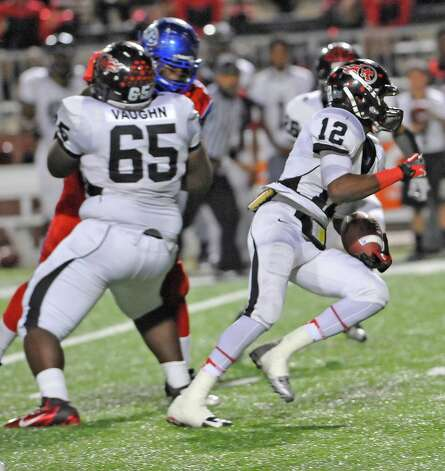 "Titan #12, Roderic Rucker, right, heads for the goal while his teammate #65, Brendan Vaughn, left, stops a West Brook defender.   The West Brook Bruins hosted the Port Arthur Memorial Titans football team Friday night at the Carrol A. ""Butch"" Thomas Educational Support Center Beaumont.  This was a District 21-5A game. At the half, the score was the Titans 35, the Bruins 10.  Dave Ryan/The Enterprise"
