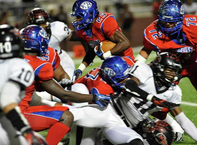 "West Brook Bruin #25, Justin Hervey, center, heads for a hole that his teammates opened up for him to run through. The West Brook Bruins hosted the Port Arthur Memorial Titans football team Friday night at the Carrol A.""Butch"" Thomas Educational Support Center Beaumont.  This was a District 21-5A game. At the half, the score was the Titans 35, the Bruins 10.  Dave Ryan/The Enterprise Photo: Dave Ryan"