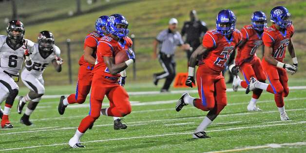 "West Brook Bruin #25, Justin Hervey, center, heads downfield with the Titan defenders right on his heels. The West Brook Bruins hosted the Port Arthur Memorial Titans football team Friday night at the Carrol A.""Butch"" Thomas Educational Support Center Beaumont.  This was a District 21-5A game. At the half, the score was the Titans 35, the Bruins 10.  Dave Ryan/The Enterprise Photo: Dave Ryan"