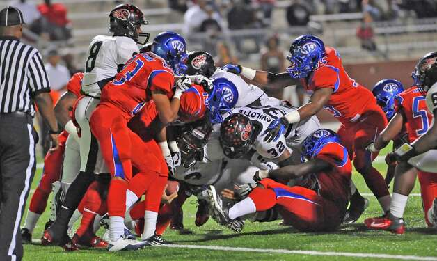 "The West Brook Bruin defense holds Titan #3, Matthew Romar, center, at the one yard line despite the efforts of his teammates. The West Brook Bruins hosted the Port Arthur Memorial Titans football team Friday night at the Carrol A.""Butch"" Thomas Educational Support Center Beaumont.  This was a District 21-5A game. At the half, the score was the Titans 35, the Bruins 10.  Dave Ryan/The Enterprise Photo: Dave Ryan"