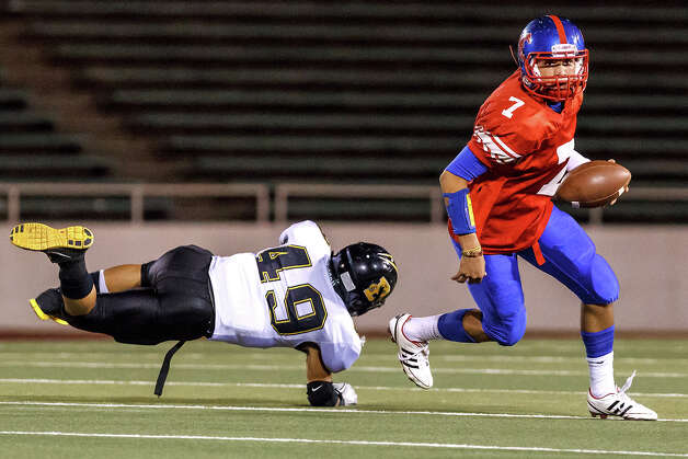Jefferson quarterback Jorge Flores (right) eldues a tackle by Brennan's Michael Huron as he rolls out looking for a receiver during the first quarter of their game at Alamo Stadium on Nov. 2, 2012.  Brennan won the game 14-0.  MARVIN PFEIFFER/ mpfeiffer@express-news.net Photo: MARVIN PFEIFFER, Express-News / Express-News 2012