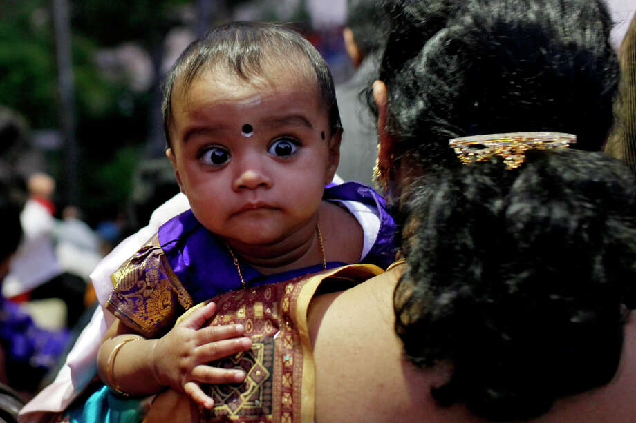 Jayanthi Kota carries her six-month-old daughter, Sri Tanvi, down the stairs at the Arneson River Theater for the first city-wide celebration of Diwali: the Festival of Lights in San Antonio on Sunday, Nov. 1, 2009. Photo: Lisa Krantz, SAN ANTONIO EXPRESS-NEWS / lkrantz@express-news.net