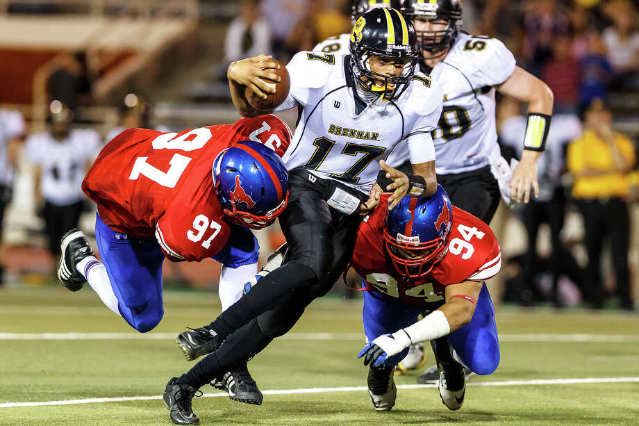 Brennan's Da'Shawn Key (center) tries to elude Jefferson's Arthur Garcia (left) and Mike Garcia as he takes off on a quarterback keeper during the fourth quarter of their game at Alamo Stadium on Nov. 2, 2012.  Brennan won the game 14-0.  MARVIN PFEIFFER/ mpfeiffer@express-news.net Photo: MARVIN PFEIFFER, Express-News / Express-News 2012
