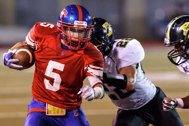 Jefferson's Mark Mangel tries to get past Brennan's Jushua Luna after a reception during the first quarter of their game at Alamo Stadium on Nov. 2, 2012.  Brennan won the game 14-0.  MARVIN PFEIFFER/ mpfeiffer@express-news.net Photo: MARVIN PFEIFFER, Express-News / Express-News 2012