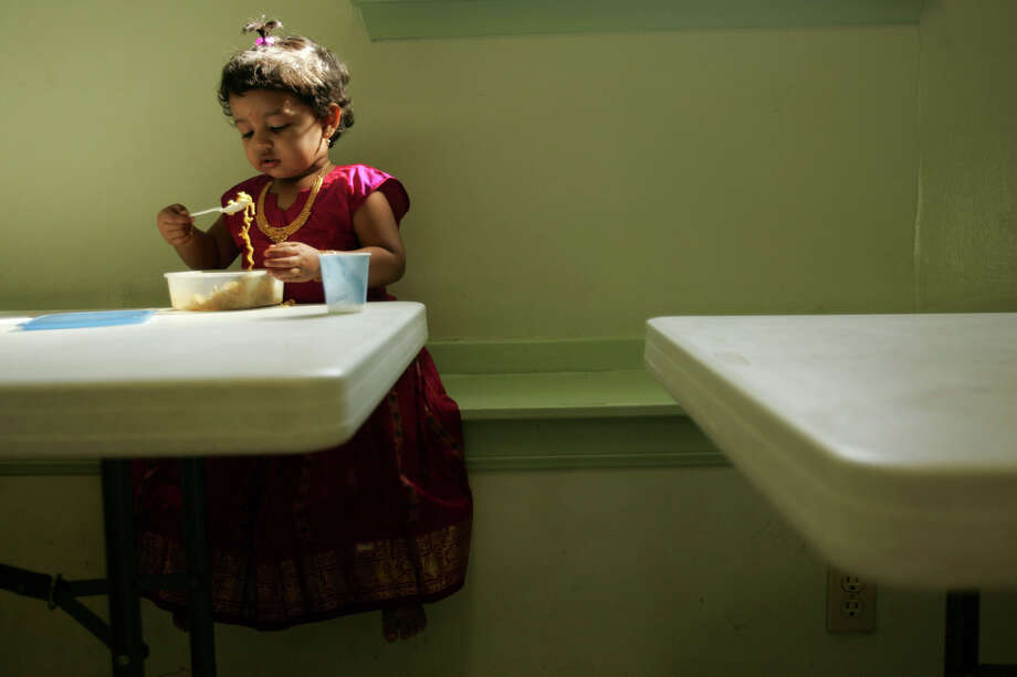 Shreya Rajagopalan, 2, has a snack during during the Diwali celebration, known as the Festival of Lights marking the Hindu New Year, at the Hindu Temple of San Antonio in Helotes on Nov. 6, 2005. Photo: Lisa Krantz, San Antonio Express-News / SAN ANTONIO EXPRESS-NEWS