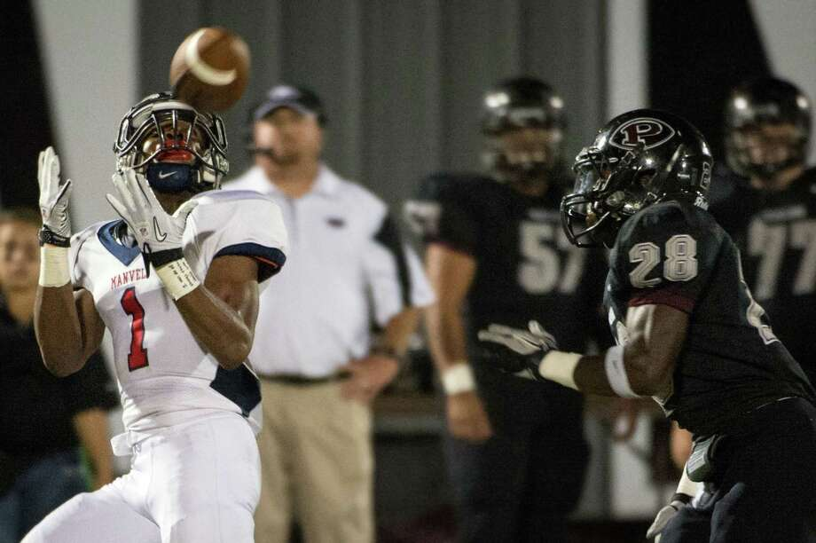 Manvel wide receiver Carlos Thompson, left, pulls in a 64-yard touchdown pass over Pearland defensive back Marlon Walls in the first quarter Friday. Thompson caught two of Shane McCarley's five touchdown passes. Photo: Smiley N. Pool, Staff / © 2012  Houston Chronicle