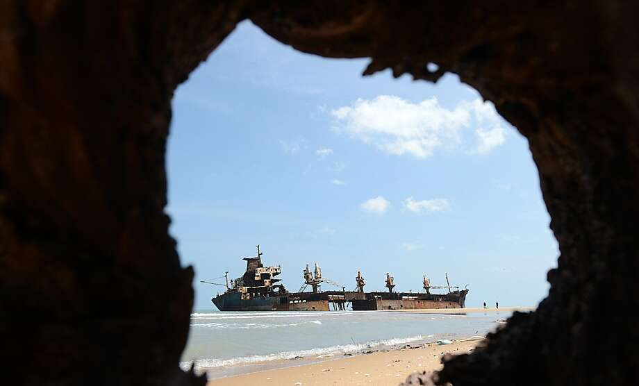 The wreckage of the Jordanian ship Farah-3, which ran aground after being captured by Tamil Tiger rebels in December 2006, is seen in the background as unseen Sri Lankan troops uncover a cache of weapons exposed by recent storm surges and heavy rains near the north-eastern town of Vellamullivaikkal in the Mullaittivu district on November 2, 2012. A storm surge in Sri Lanka's northeast has exposed buried artillery guns of Tamil Tiger rebels in a region where the final battles of the country's 37-year conflict were fought, the army said. Troops stumbled on four 152mm artillery barrels and one 130 mm piece believed to have been used by Tiger guerrillas during their last stand in the district of Mullaittivu, army spokesman Ruwan Wanigasooriya said. Photo: Ishara S.kodikara, AFP/Getty Images