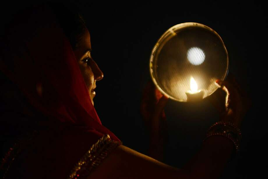An Indian Hindu woman poses while performing a ritual on the occasion of the Hindu festival of Karva Chauth (Husband's Day) in Amritsar on November 2, 2012. Married women observe Karvachauth by fasting and offering prayers seeking welfare, prosperity, and longevity of their husbands. Photo: Narinder Nanu, AFP/Getty Images