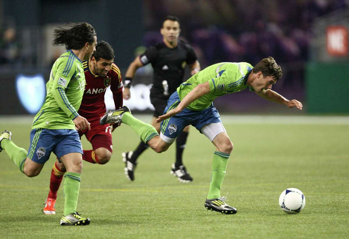Seattle Sounders player Brad Evans is tripped up by Real Salt Lake player Javier Morales (11) in a play that resulted in a yellow card for Morales during an MLS Western Conference semifinal on Friday, November 2, 2012 at CenturyLink Field in Seattle.